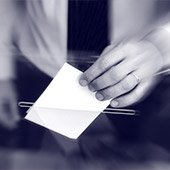 Voter dropping ballot into a box