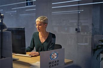 Woman from MCAO CARU Working at a Computer