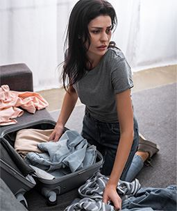 Female domestic violence victim packing suitcase with clothing