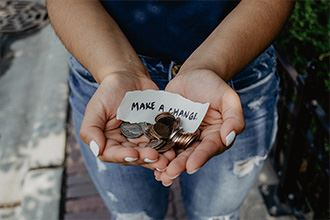 Person holding coins with message on paper: Make a Change